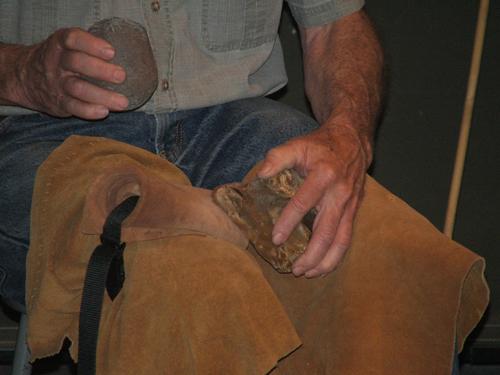 Hammer stone in hand, Bob prepares to strike a flake off a chert core