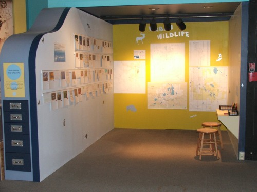 The Urban Wildlife exhibit, with photos on the left wall and maps on the back wall